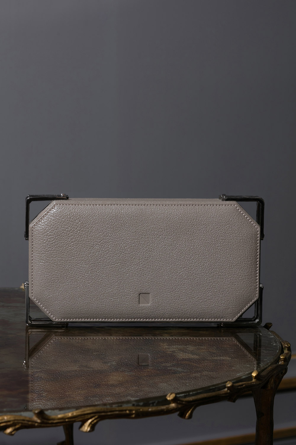 Grey geometric leather and metal clutch bag